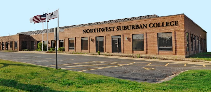 A brick building with American flags waving out front. For an allied healthcare school in Chicagoland call NWSC.