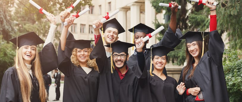 A group of multicultural students holding their diplomas in the air cheering, while wearing a cap and gown with red accents