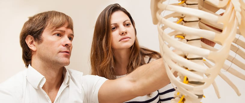 A teacher and student examining a model skeleton