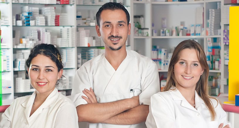 Three Pharmacy Technician students smile and stand in a medical office
